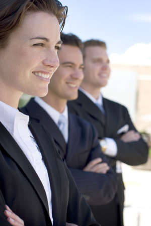 one female two males wearing dark business suits in a row smiling Imagens - 1997215