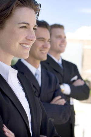 vertical: una mujer dos hombres llevaban trajes oscuros de negocios en una fila sonriendo  Foto de archivo