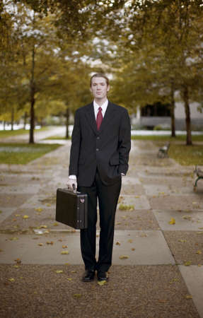 savvy: portrait of one businessman dressed in full suit standing in middle of walkway with trees and building in background