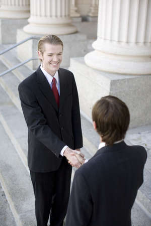 over the shoulder view of two businessmen on the steps of courthouse shaking hands Stock Photo