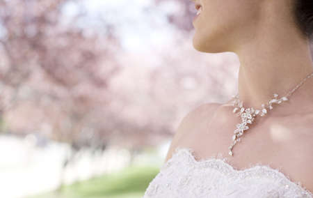 Close-up view of woman wearing wedding dress and necklace in front of pink blossom trees, looking away, head and shoulders Stock Photo