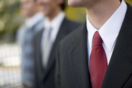 Businessmen standing together in a row looking smiling in same direction, well-dressed