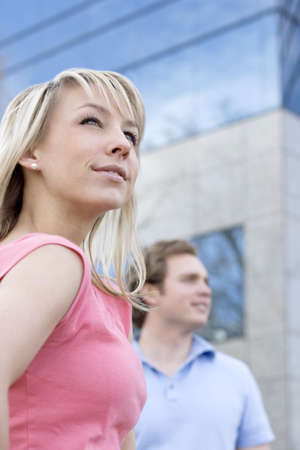 looking away from camera: one young woman and one young man standing side by side looking away from camera in front of blue and gray office building