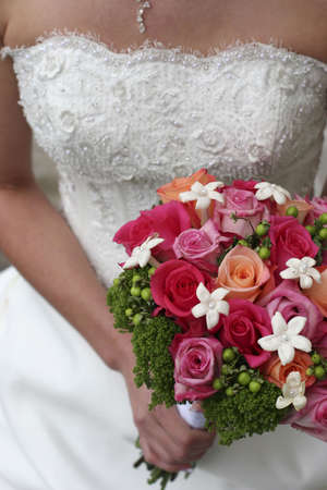 young woman dressed in wedding dress wearing necklace and holding bouquet of roses, mid-section photo
