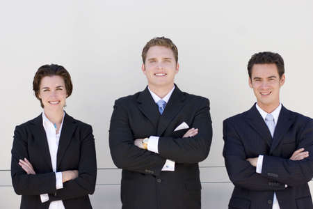 three business people standing side by side looking at camera smiling with white background photo