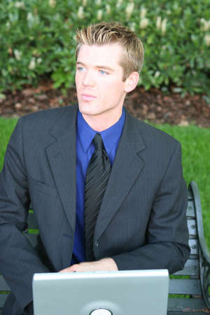 waistup: close-up waist-up view of young blue blond hair businessman sitting on bench holding laptop looking away