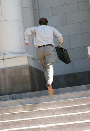 rear view of full body businessman carrying briefcase running up flight of stairs into courthouse building