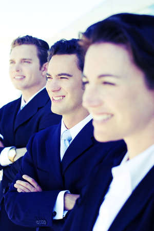close-up shot of three businesspeople standing side by side smiling in full business suits