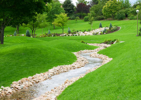 stream of water flowing through grassy hills with trees Stock Photo