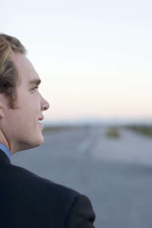 road shoulder: over the shoulder shot of young businessman looking sideways smiling wearing business suit in the middle of a road in the desert
