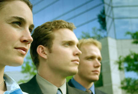 unified: Three business people standing in a row standing in front of a blue business building all looking in the same direction