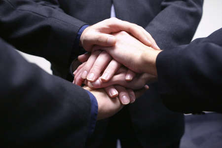 Business people with their hands together in teamwork Stock Photo