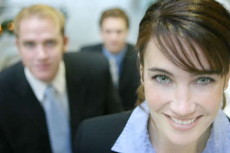 staggered: three business people looking at camera staggered on stairs