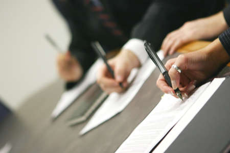 negotiation business: three hands holding pens signing document on table Stock Photo