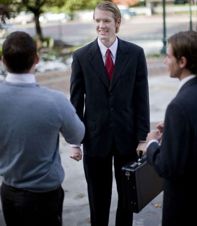 three business men talking standing outdoors