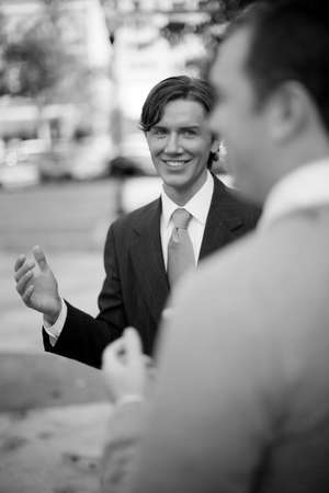 over the shoulder view: over shoulder view of businessman standing in suit and tie talking