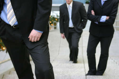 three business people standing on steps faced forward photo
