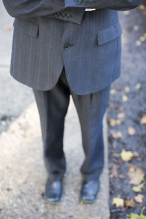 folding arms: waist-down front shot of businessman folding arms wearing suit standing on sidewalk