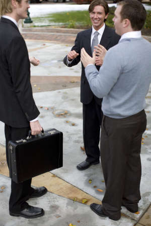 expertise: three businessmen standing talking outdoors