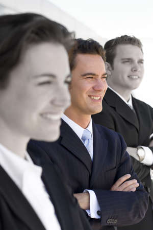 three business people standing in a row looking in same direction Stock Photo