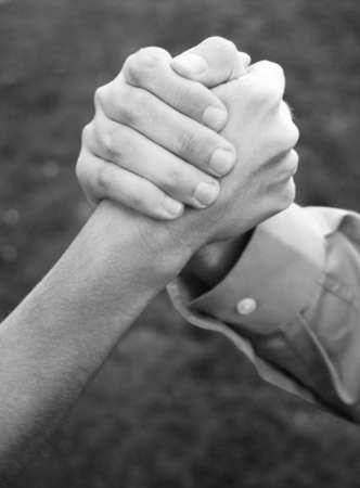 clasping: close up of two hands clasping with green grass in background