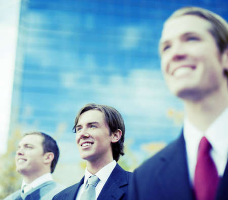 three business men standing and smiling in same direction