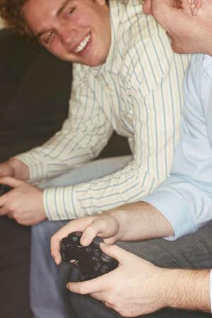 jugando videojuegos: dos j�venes sentados jugando juegos de video  Foto de archivo