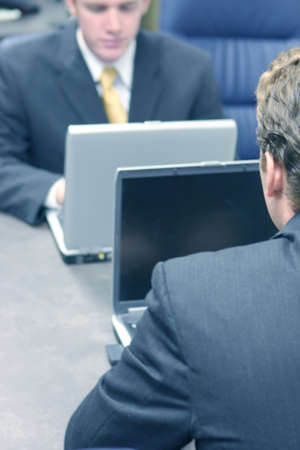 two young businessmen sit across from each other looking down at their laptops Stock Photo