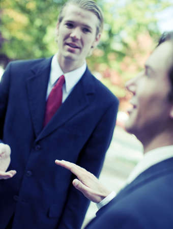 two businessmen standing talking outdoors photo