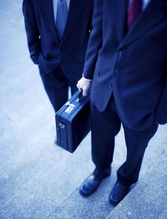 two businessmen standing on steps with hands in pockets and holding briefcase no faces