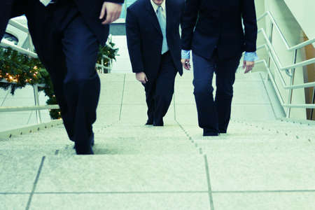 three business people walking up steps