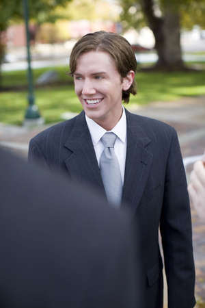 over the shoulder view: over shoulder view of two businessman standing and smiling
