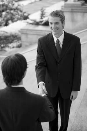two businessmen standing on steps smiling and shaking hands
