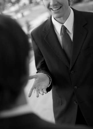 over the shoulder view: over shoulder view of businessman talking, standing in suit and tie Stock Photo