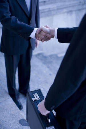 two businessmen standing shaking hands on steps