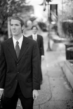 staggered: two businessmen staggered one behind the other in full suits Stock Photo
