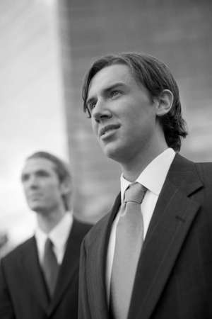two businessmen standing side by side looking forward in front of tall blue office building photo