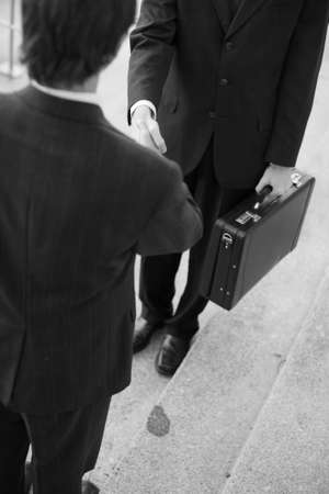 two businessmen standing on steps shaking hands photo