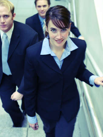 three business people looking towards camera and walking up stairs Imagens - 2670074