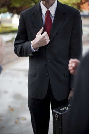 over the shoulder view: over shoulder view of businessman in suit standing holding briefcase and part of his jacket