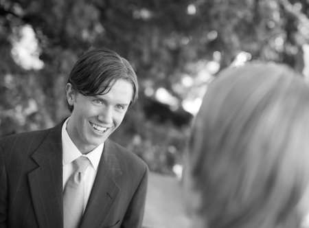 over the shoulder view: over shoulder view of businessman standing in suit and tie smiling
