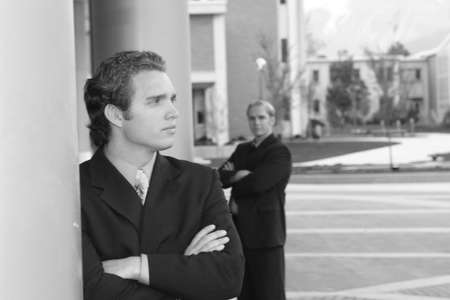 two businessmen standing in full suits with folded arms