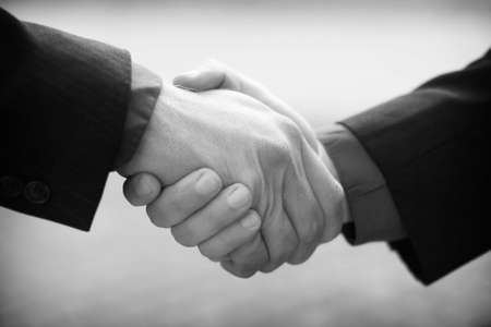 Firm business handshake with red and blue shirts and black suits against gray background Stock Photo - 2748487