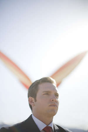Single white businessman standing and looking forward with giant  wings in background
