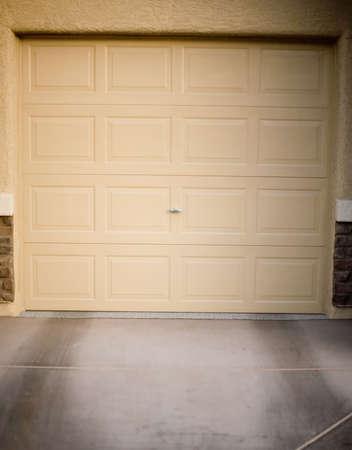 Closed tan garage door with tan building exterior