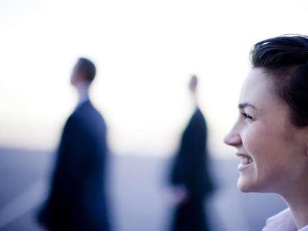 Trois hommes d'affaires debout ensemble dans une rangée regardant dans la même direction souriant