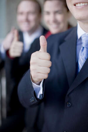 Three businesspeople standing and smiling giving thumbs up.