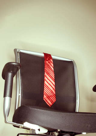 Red tie on business chair in office 版權商用圖片