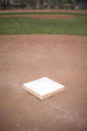 ballgame: Individual baseball base in baseball diamond with green grass Stock Photo