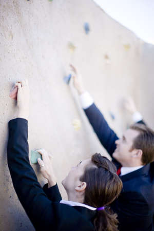 Three businesspeople in suits climbing wall to reach top